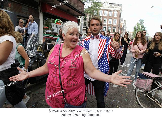 Revelers on the street in the Prinsengracht canal participating in the Amsterdam Canal Parade during Amsterdam Gay Pride on August 5 , 2017 in Amsterdam
