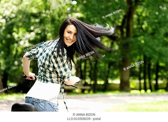 Happy young woman with bike in the park, Debica, Poland
