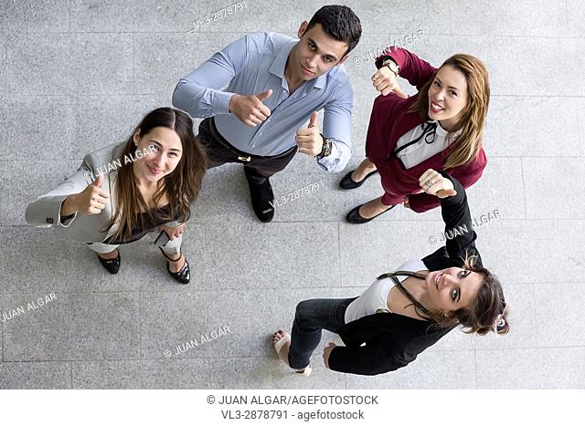 The group of colleagues looking up and gesturing the thumbs up in the office. Horizontal indoors shot