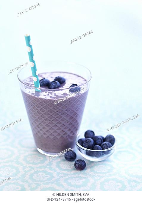 A blueberry smoothie with a straw in a glass