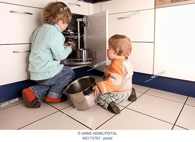 Boys playing with pots and lids in kitchen. Germany