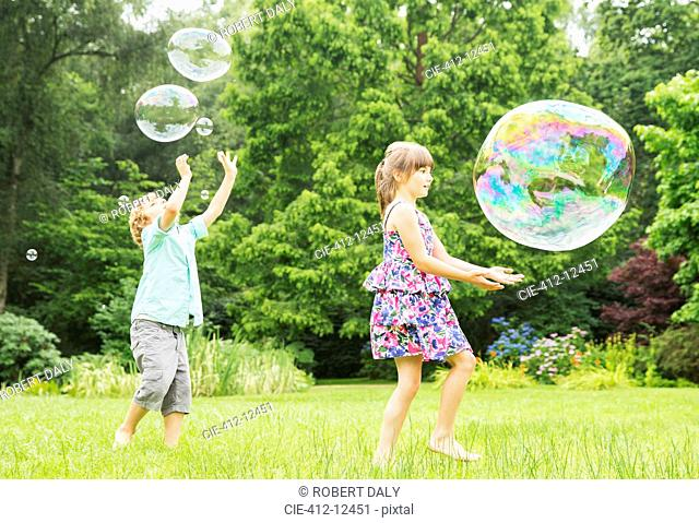 Children playing with bubbles outdoors