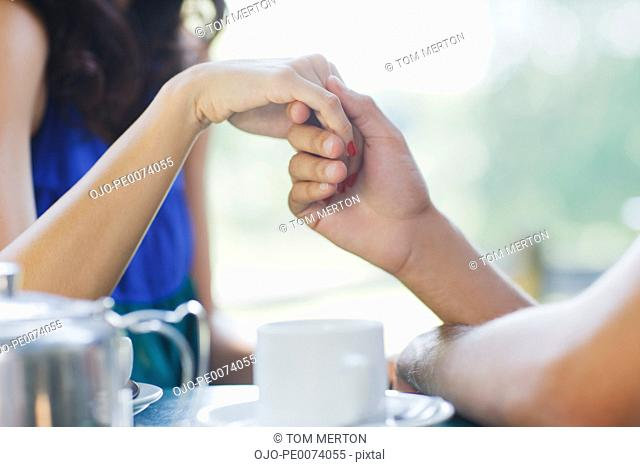 Couple having tea and holding hands