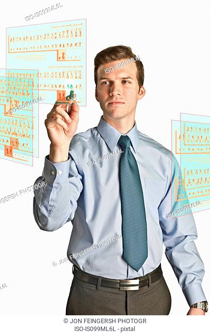Businessman interacting with holographic screens showing chromosomes