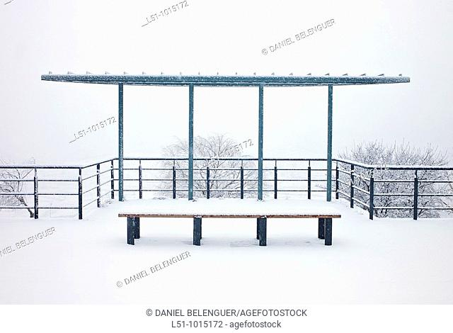 Bus stop snow-covered on Morella, under a snowfall