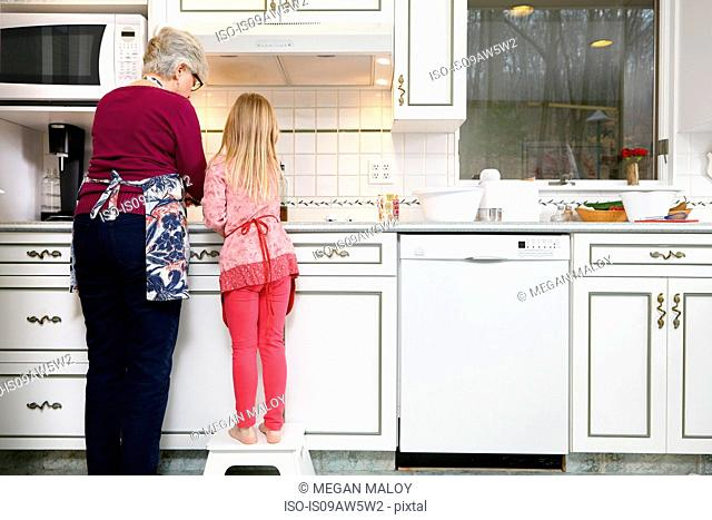 Rear view of girl and grandmother standing at kitchen hob