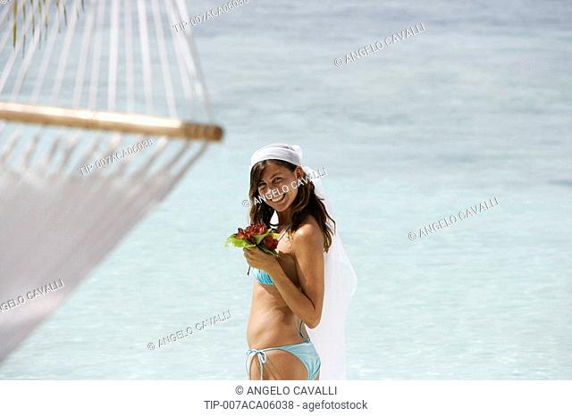 Woman in bikini with bouquet and veil