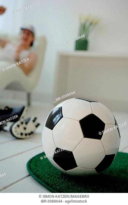 Football lying on grass carpet in the living room, football fan sitting on a sofa