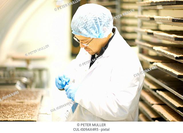 Side view of worker wearing hairnet and latex gloves collecting samples in plastic bag