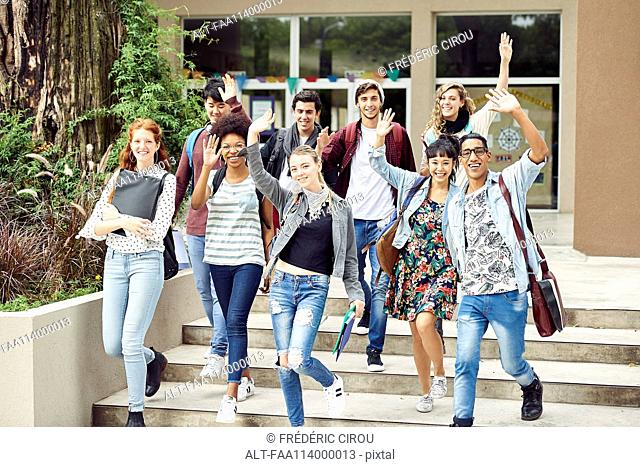 College students waving while walking on campus