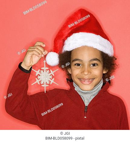 Mixed Race boy holding Christmas ornament