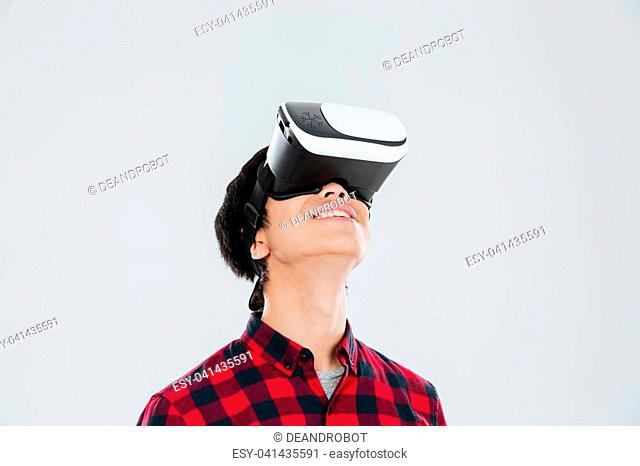 Picture of cheerful young asian man dressed in casual shirt in a cage and wearing virtual reality device. Isolated over white background