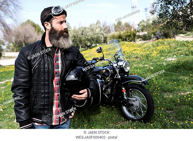 Biker standing on a meadow in front of his motorcycle