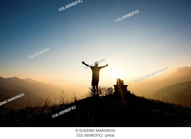 Rear view of man on mountain peak, arms raised, Passo Maniva, Italy