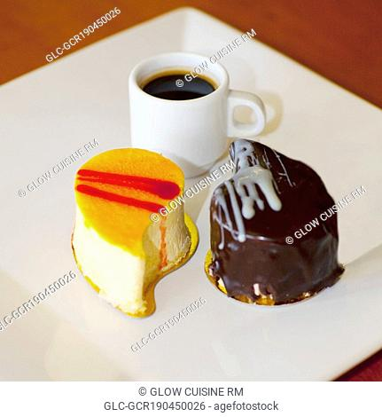 Close-up of assorted pastries with a cup of black coffee