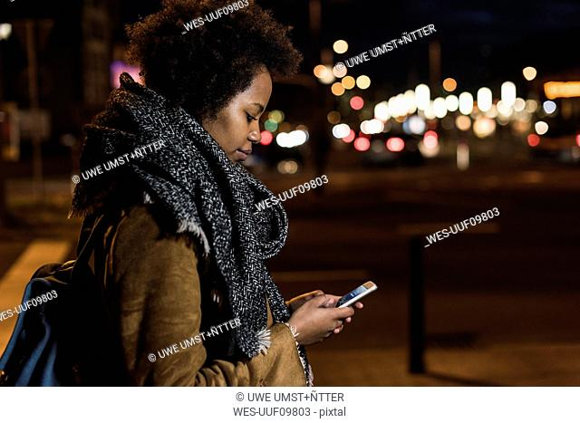 Young woman checking her smartphone by the roadside