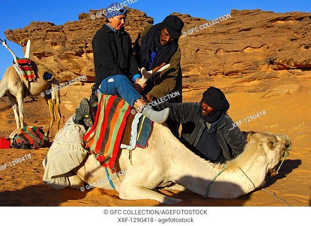 Tuareg nomads helping a female tourist to climb on a dromedary in the Acacous Mountains, Sahara desert, Libya