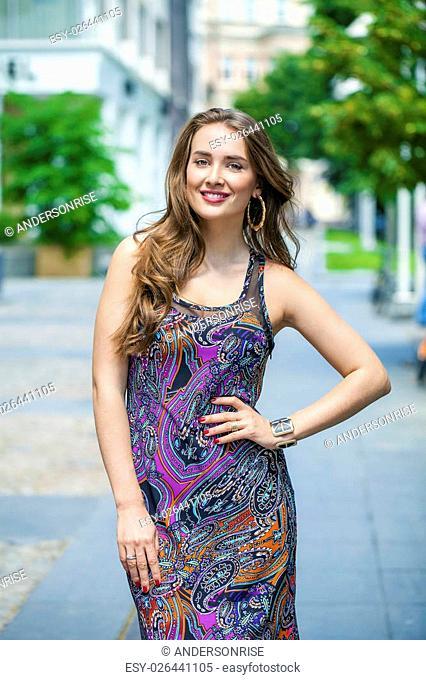 Portrait of beautiful model woman in long color dress posing summer street