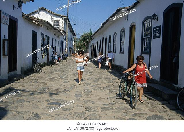 Street in town. Small white painted houses in terrace. People walking