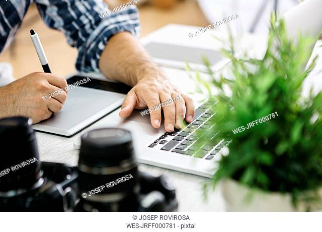 Photographer working at desk with graphics tablet, partial view