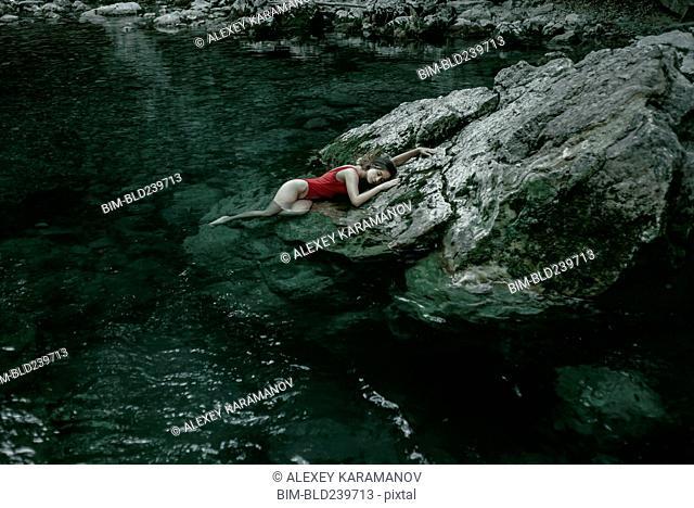Caucasian woman laying on rocks in pool of water
