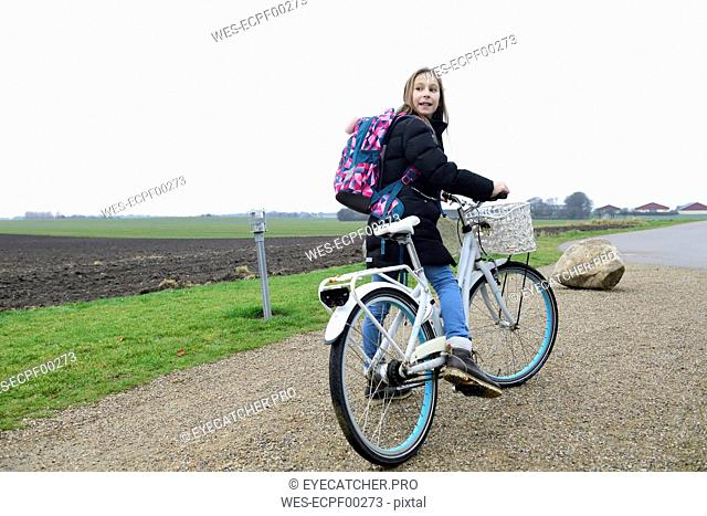 Girl with backpack and bicycle in rural landscape