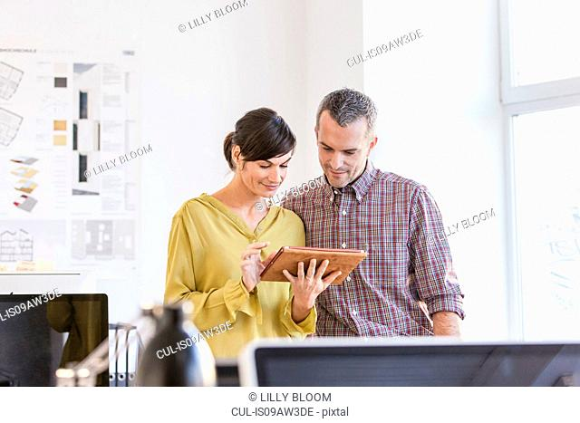 Colleagues in office looking down at digital tablet smiling