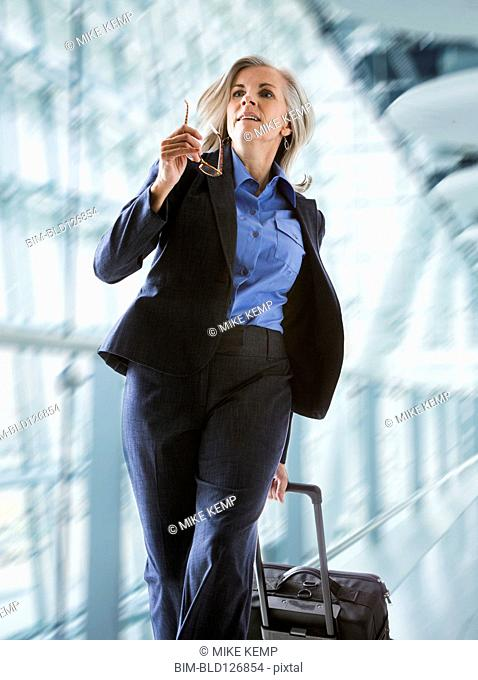 Caucasian businesswoman rushing with suitcase in airport
