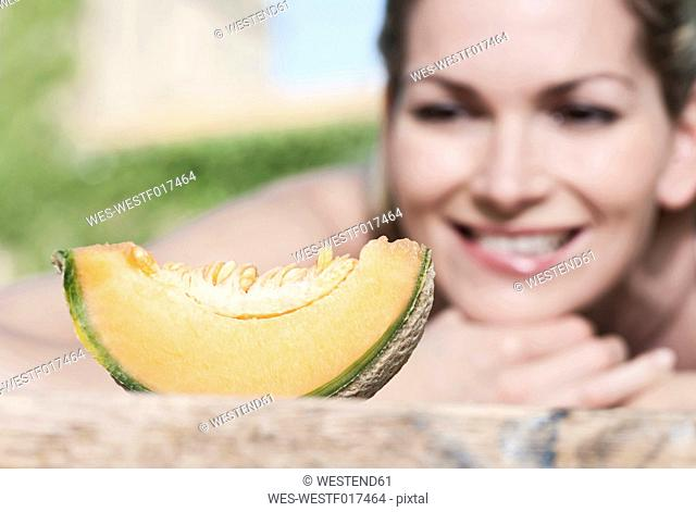 Italy, Tuscany, Magliano, Slice of honey melon in front of young woman, smiling