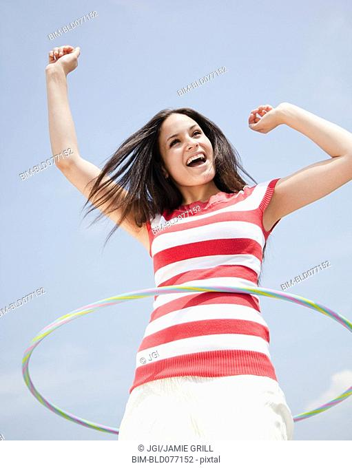 Mixed race woman spinning hula hoop