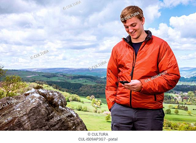 Male teenage hiker reading smartphone texts on top of Guise Cliff, Pateley Bridge, Nidderdale, Yorkshire Dales