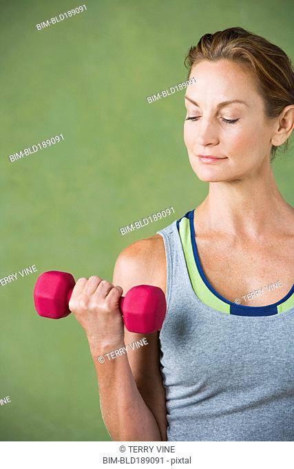 Mixed race woman lifting hand weight