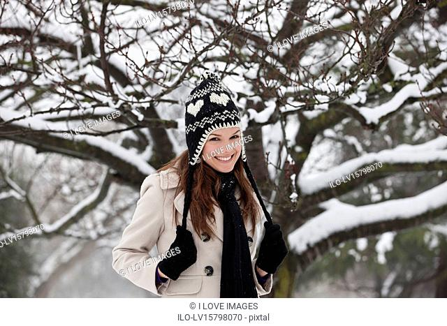 A young woman standing in the snow, smiling