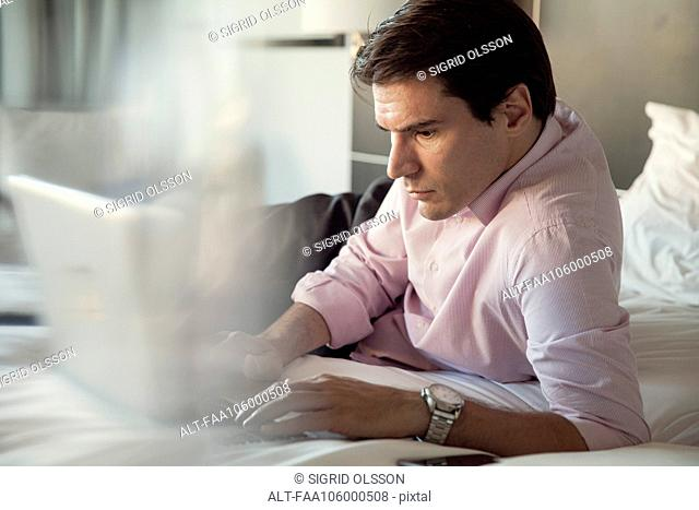 Man using laptop computer on bed