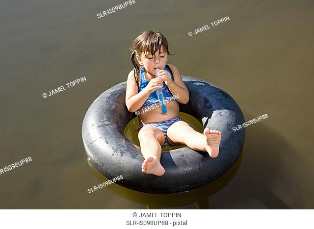 Girl eating lolly on inflatable ring in lake