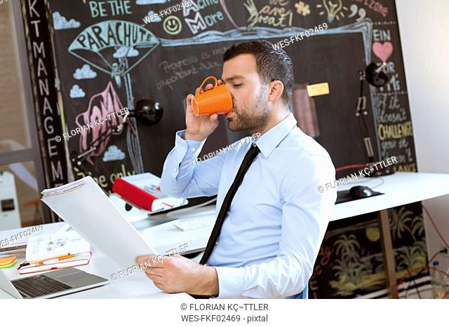 Businessman in creative office looking at documents and drinking coffee