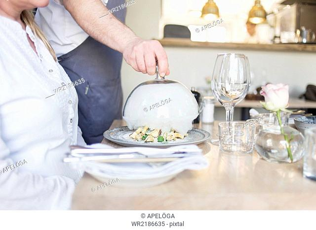 Midsection of waiter lifting cloche for customer in restaurant