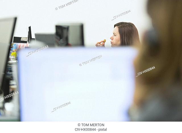 Businesswoman eating and working at desk in office
