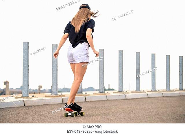 Young Beautiful Blonde Girl Riding Orange Skateboard on the Bridge