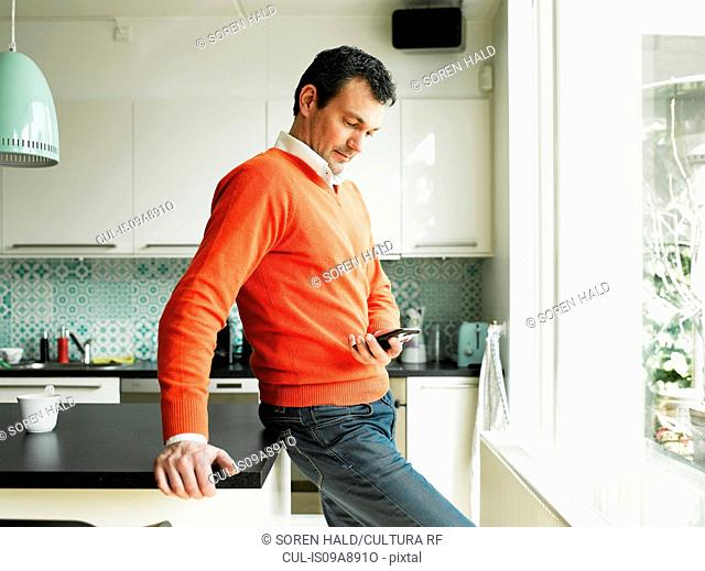 Mature man using cellphone in kitchen