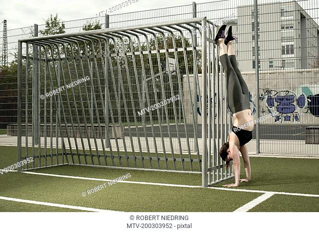 Young woman doing handstand on football ground, Bavaria, Germany