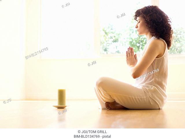 Hispanic woman meditating with candle