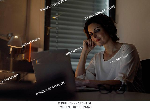 Businesswoman working overtime, using laptop