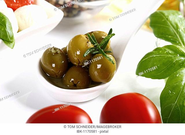 Spanish olives with thyme on a spoon, next to tomatoes and basil