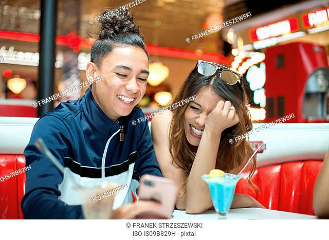 Young couple sitting in diner, looking at smartphone, laughing