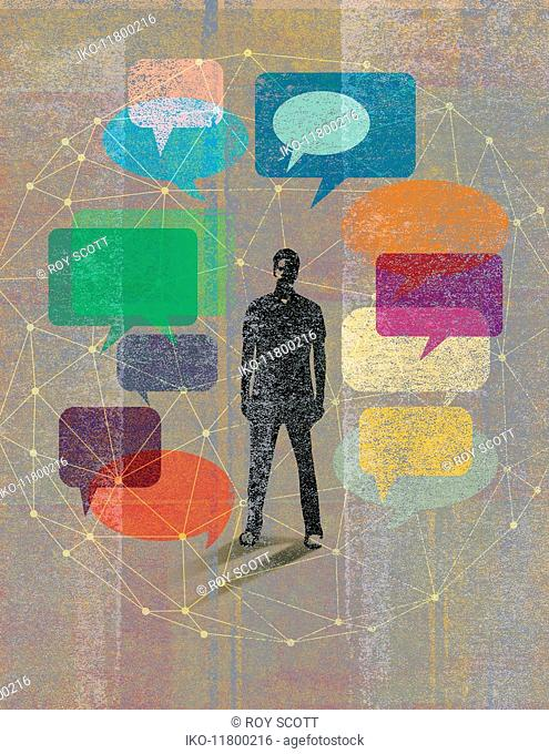 Young man surrounded by network of speech bubbles