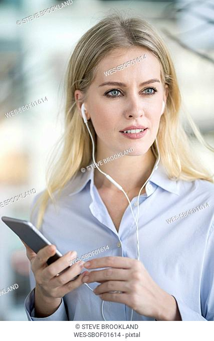 Portrait of blond woman with smartphone and earphones