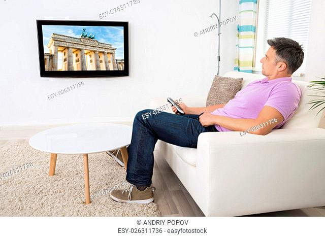 Mature Man Sitting On Couch Watching Television At Home
