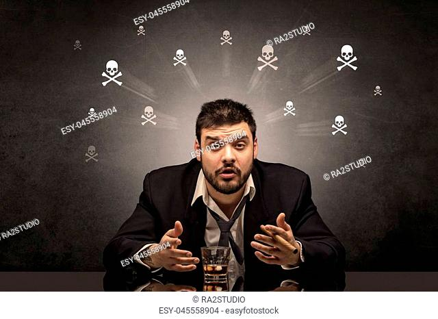 Loser drunk man sitting at table with skulls concept around