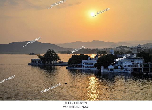 Sunset over a lake in Udaipur. Traditional historic buildings and an orange glow cast by the setting sun